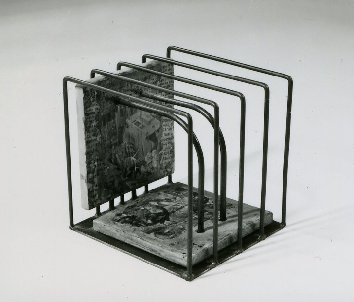 A cube of metal tubes. Wooden handwritten and photocollaged panels threaded through holes on 2 tubes.