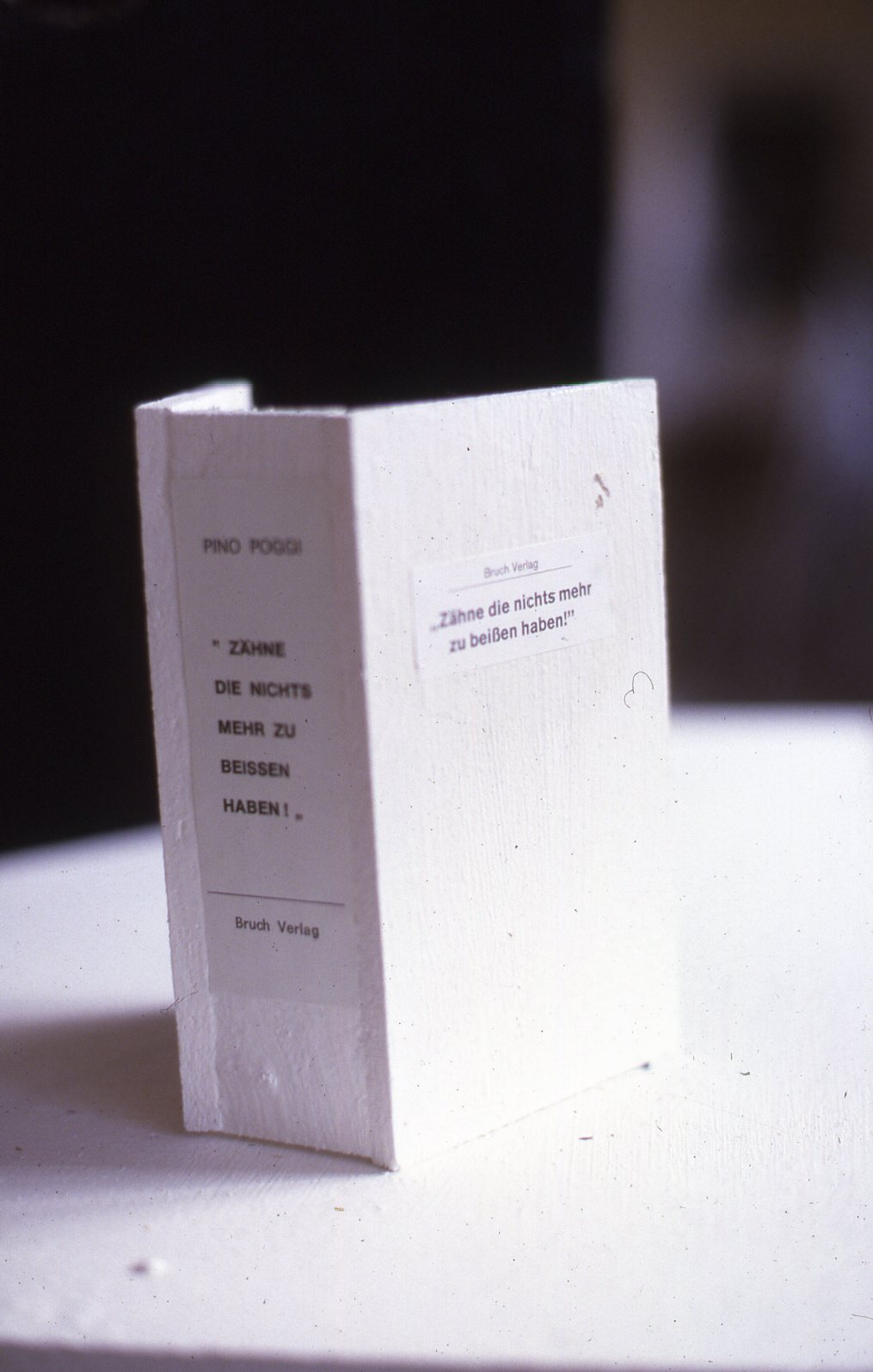 A white empty book cover made from plaster. Small paper pieces with title on the cover.