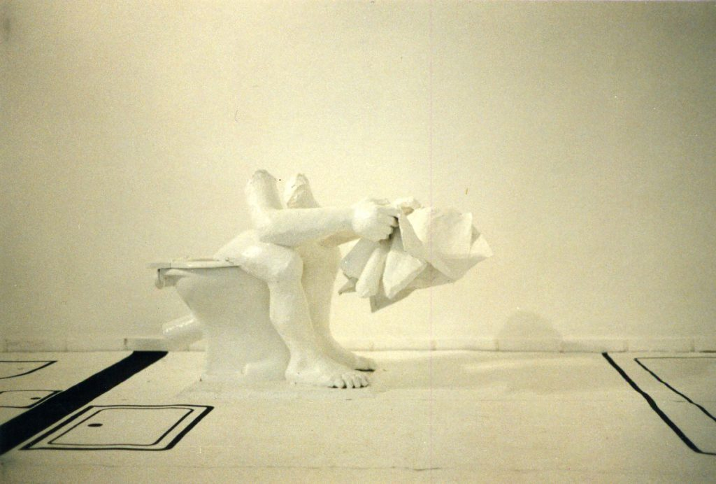 Fragmented white toilet sculpture with legs arms and of person sitting on toilet and reading newspaper.