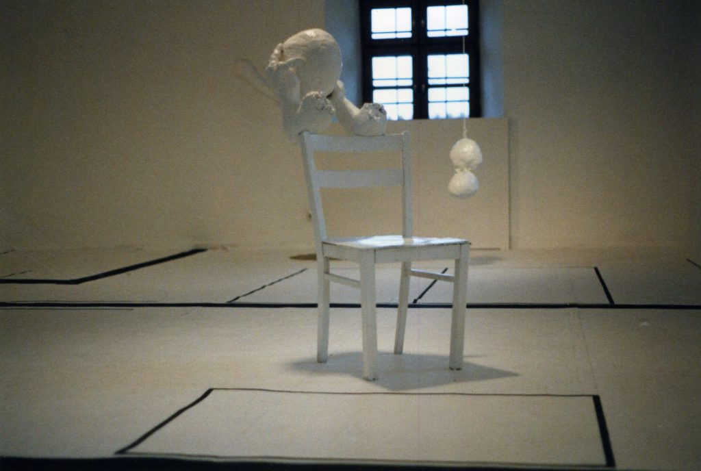 White chair with a fragmented sculpture on top behind a hanging sculpture.