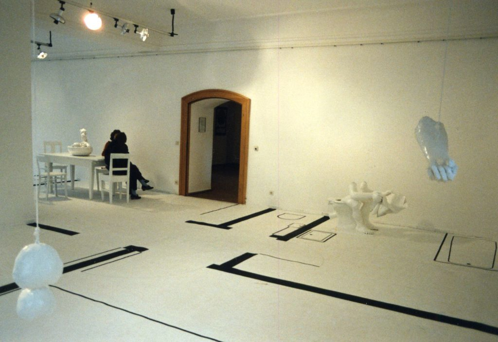 White gallery room with ground plan of a flat drawn onto the floor.