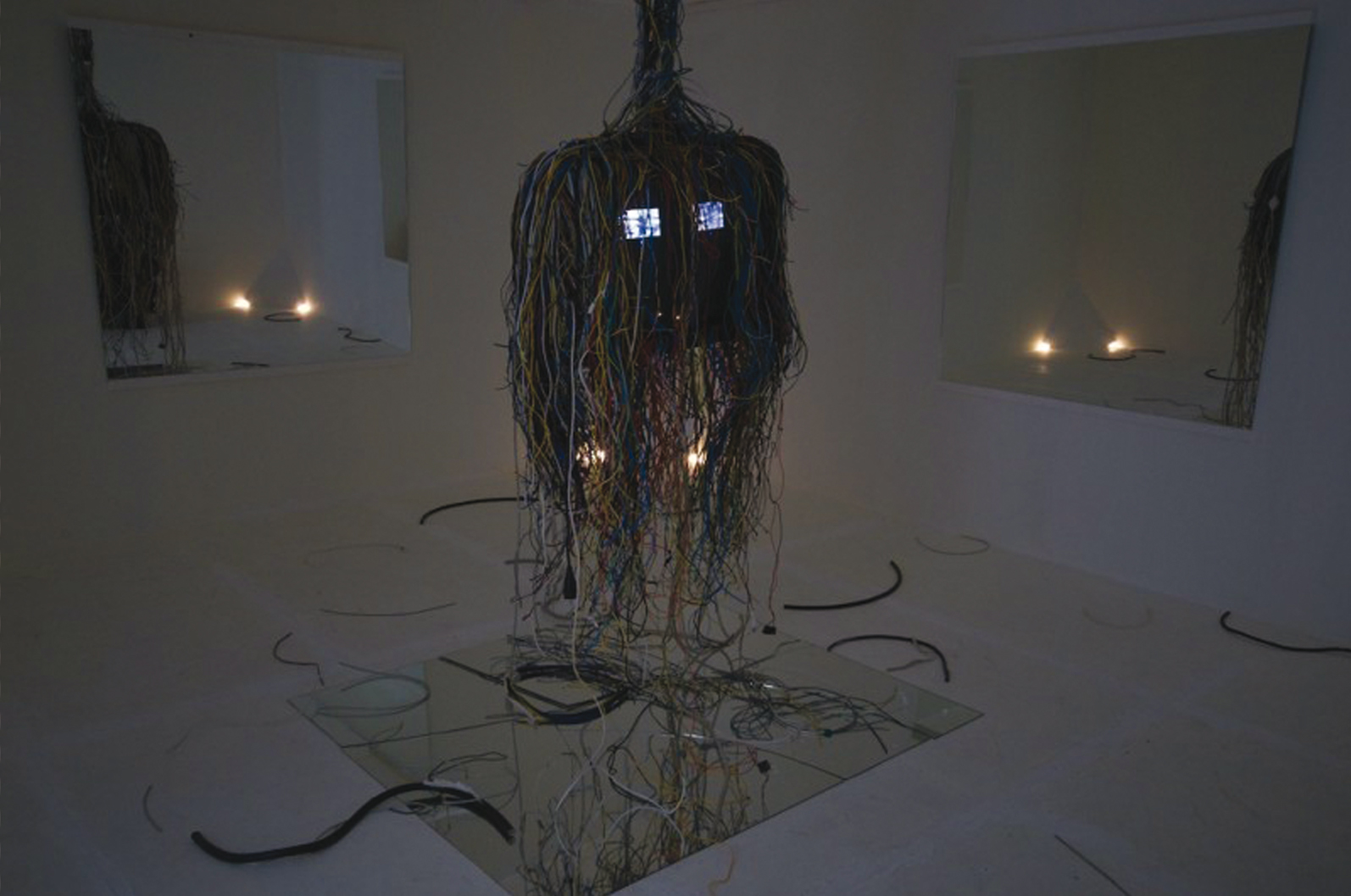 A tube television hangs in the middle of the gallery room. Numerous cables hanging down from the TV almost covering it totally. Two small screens are visible on the front screen. Huge mirrors are placed on the floor and the walls.