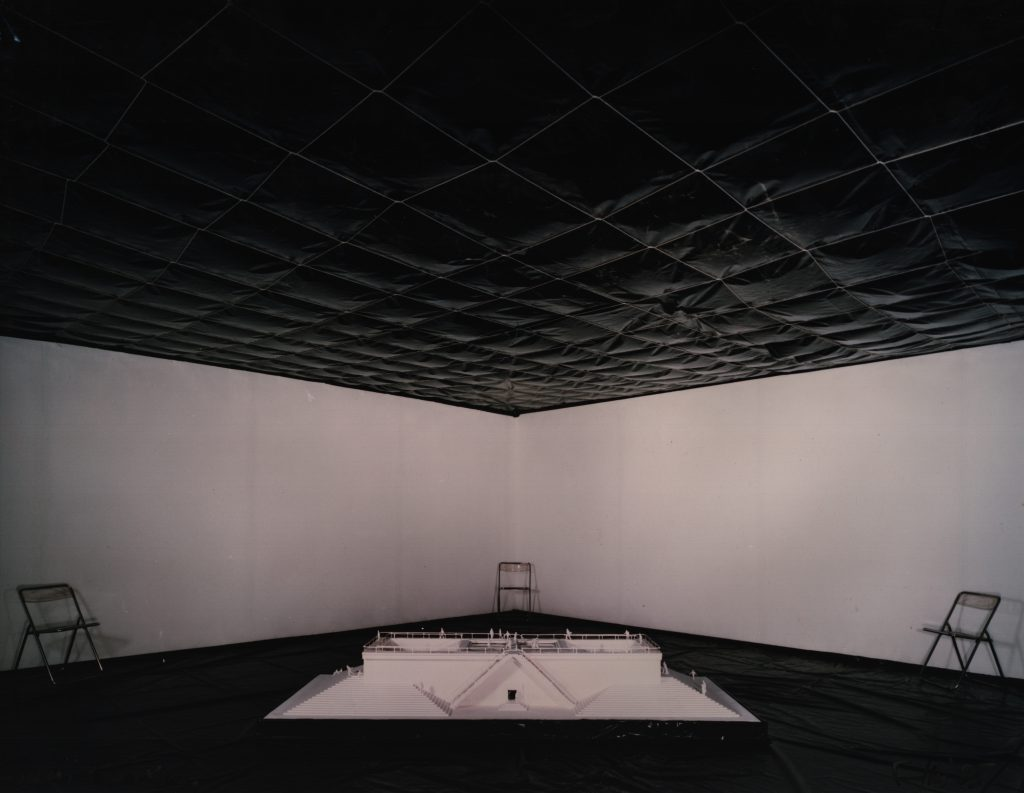 Floor and ceiling of a white room covered with black plastic foil. In the middel stands the model on the floor.