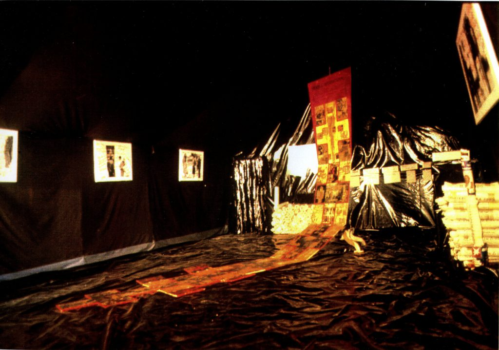 A room completely coverd with black palstic foil. A flagpole stands in the middle of the room. On the flagpole hangs an extra long banner spreading out on parts of the floor. Piles of rolled newspapers and boxes with names are placed beside the flagpole.