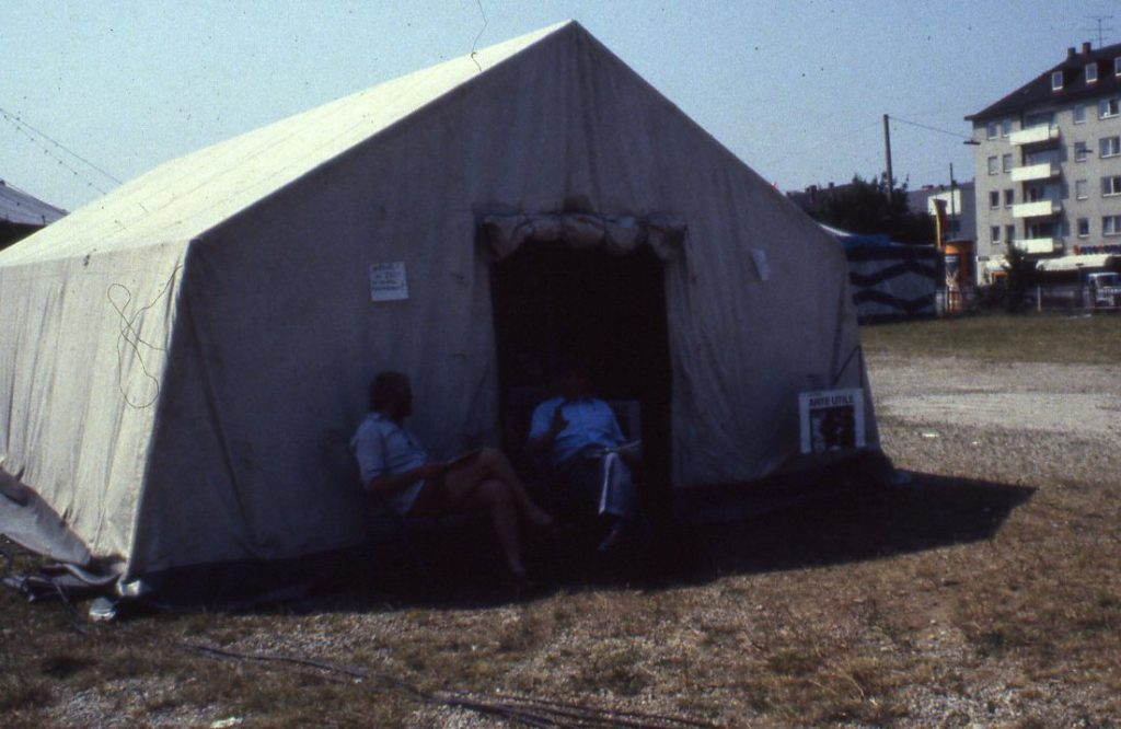 """Chairs stand beside the entrance of a large tent. A woman sits on a chair and reads a piece of paper. In the entrance area a wall of posters stating """"Arte Utile"""" prevents the look inside."""