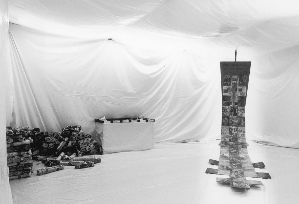A room completely coverd with white cloth. A flagpole stands on one side. On the other side piles of rolled newspapers and a table with named boxes. On the flagpole hangs an extra long banner spreading out on parts of the floor. The banner is collagd with pages of newspapers.