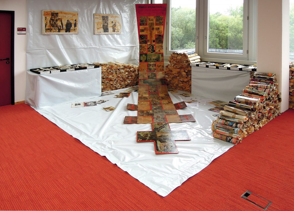 In the corner of a room everything except the windows is covered with white pastic foil. A flagpole stands in the corner. Besides piles of rolled newspapers and a table with named boxes. On the flagpole hangs an extra long banner spreading out on parts of the floor. The banner is collagd with pages of newspapers.