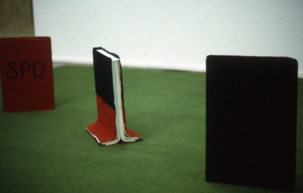 A half black half red coloured book stands in between an red and an black coloured book.