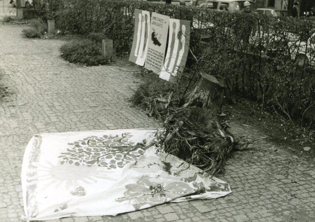 Treestump on the floor beside tree paintings on a linen cloth.