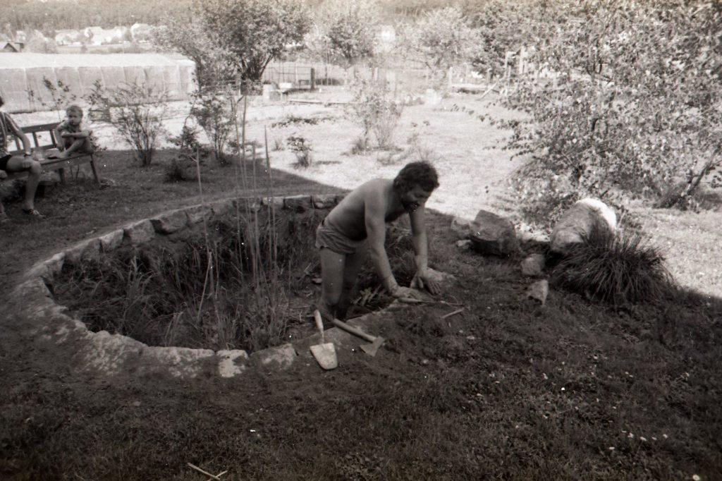 Man working inside a circular hole in the ground. Construction of a pond.