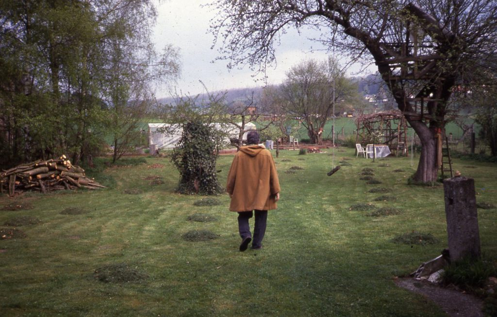 Man walking over fresh cutted lawn in the garden.