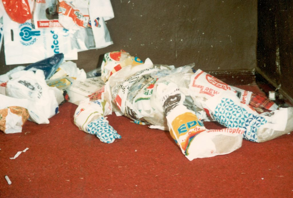 Form of a human made from plastic bags lies on the floor.