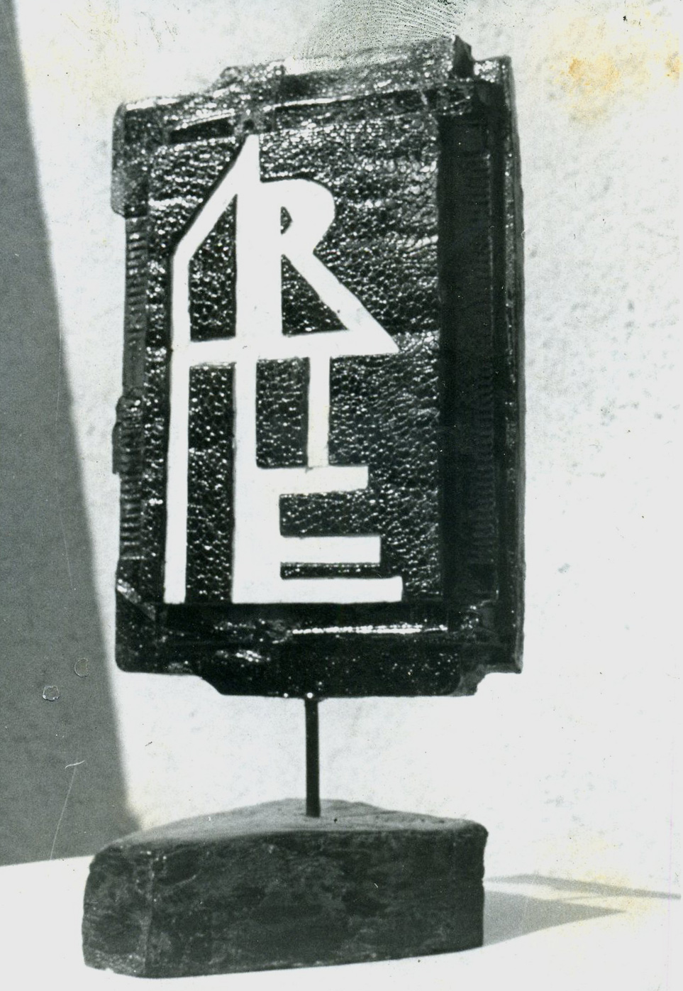 "Block of roughly layered material mounted on a stick with a base plate. Letters ""ARTE"" on front."