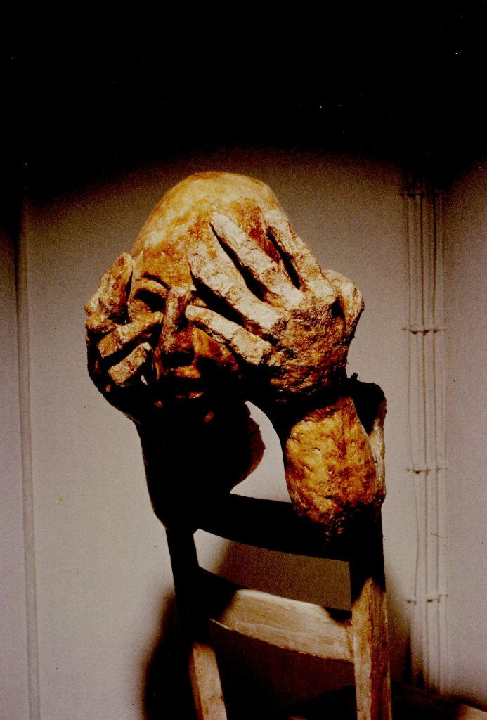 Sculpture fragments of hands holding head mounted on backrest of chair.