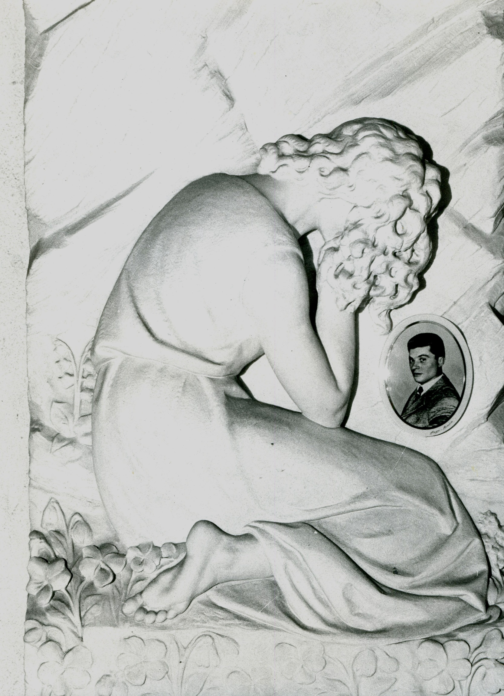 Marble fresco of a woman with hands over face. Framed portrait photo of man beside her.