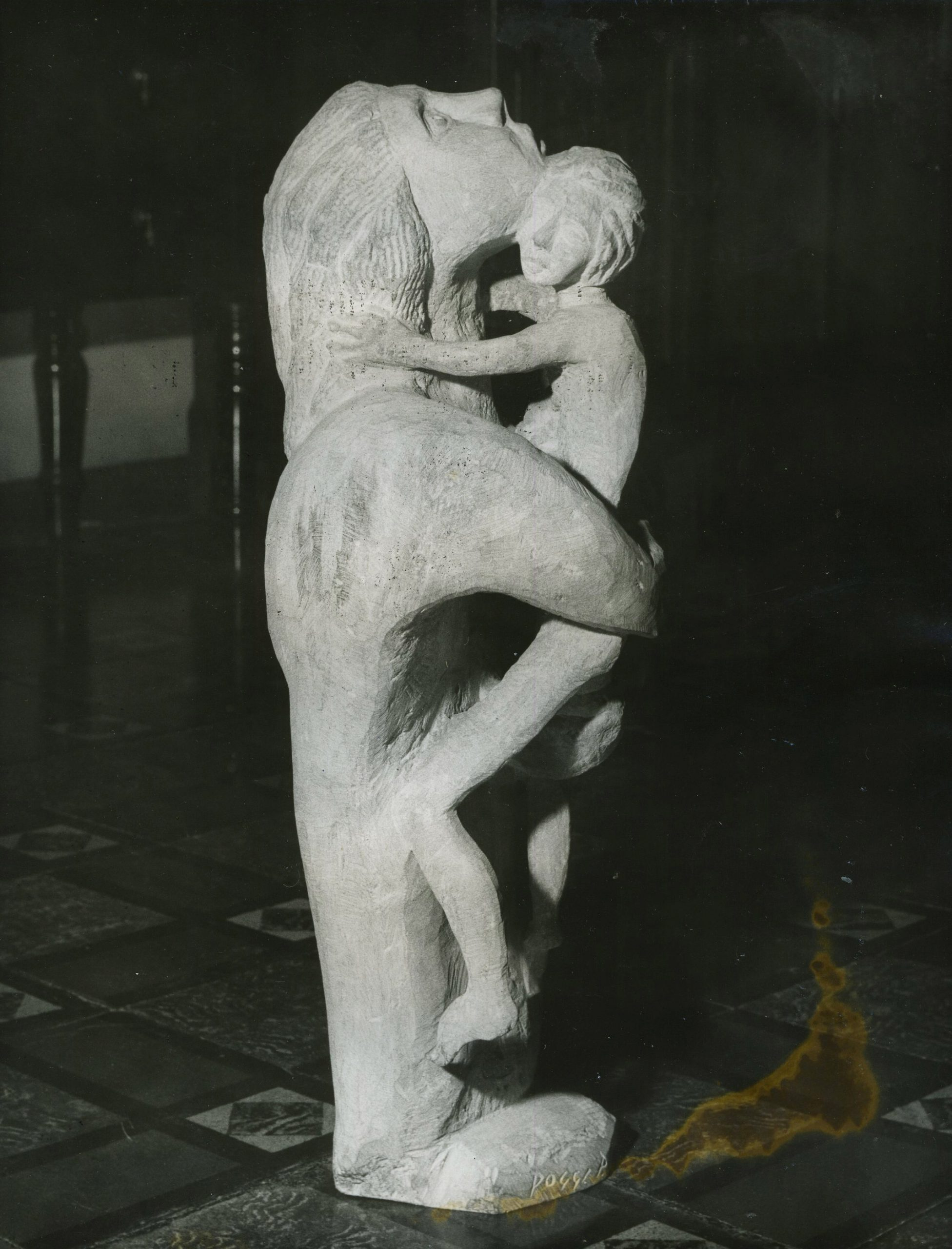 Stone sculpture of large figure looking up and holding smaller one in arms.