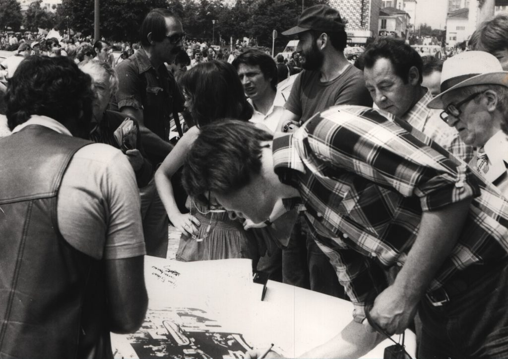 Persons standing in a circle on the street. 1 man writes on a large white sheet lying on the engine hood.
