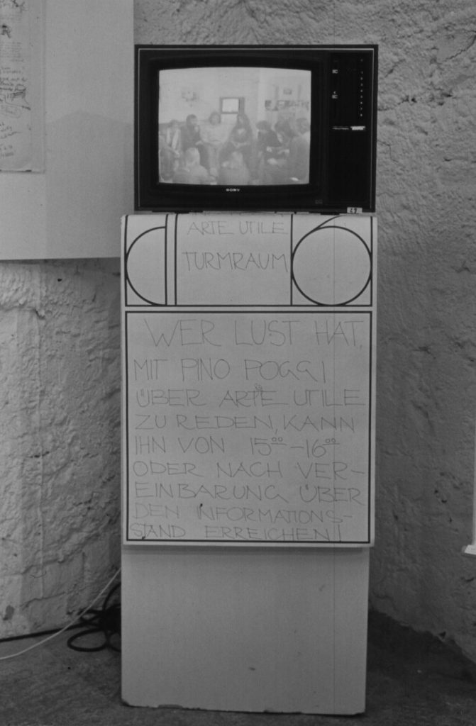 TV stands on a column. Poster with handwritten text hangs on the column.