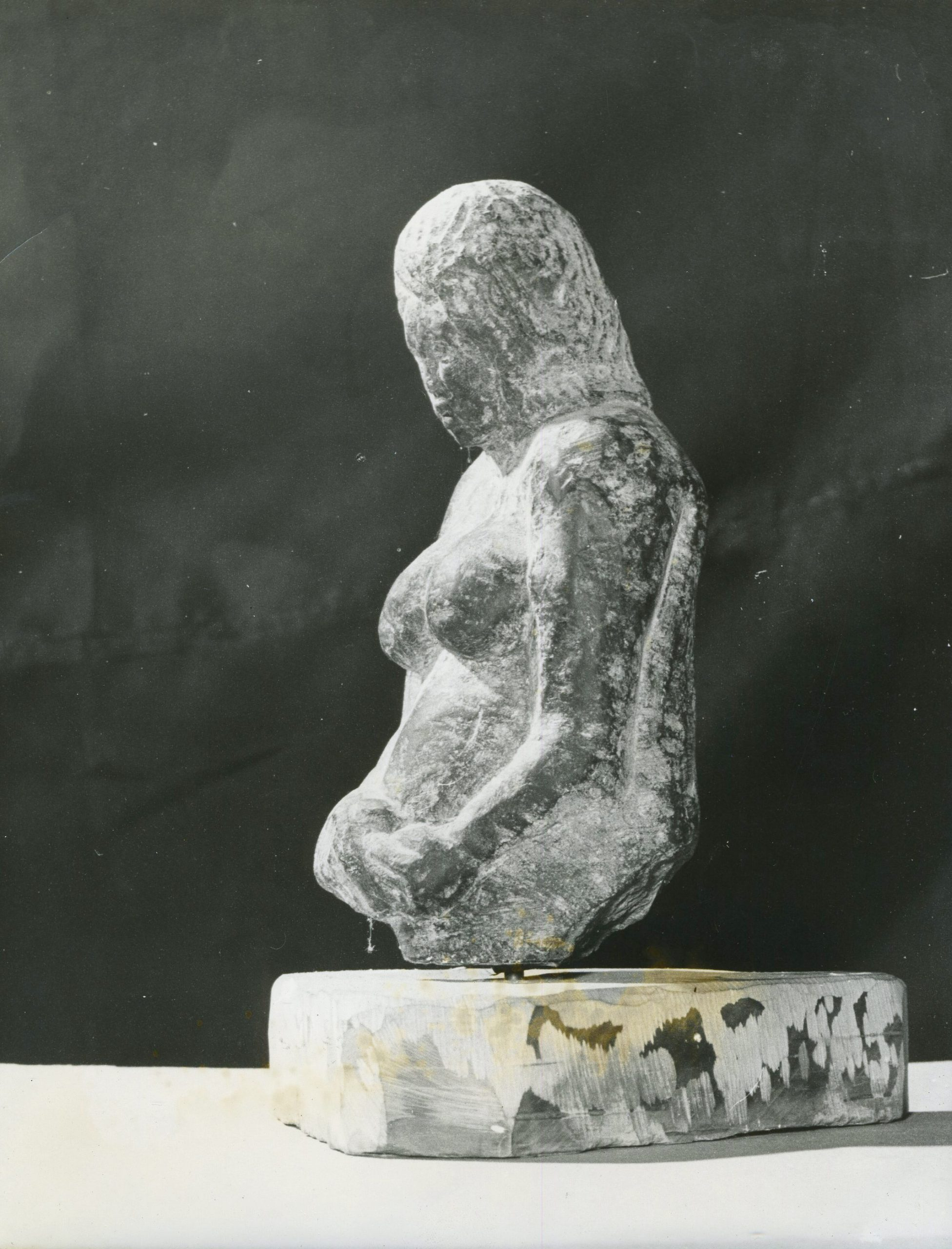Sculpture of pregnant woman. Only upper part of body.