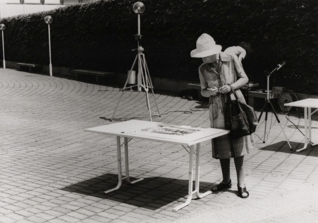 Fold-up table set-up in the street. Passing by woman looks what's on the table.