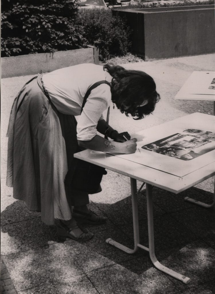 Woman writes on a sheet lying on table.