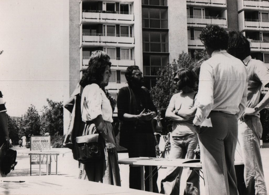 Persons discussing around a table ist-up in the street.