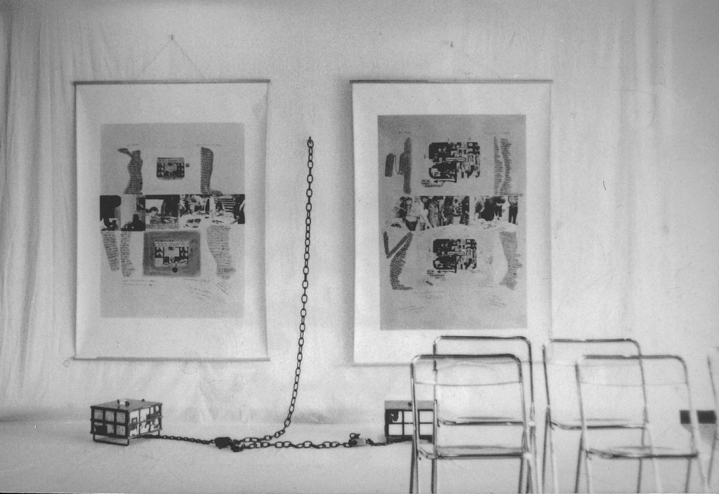 2 large sheets hang on white cloth. They picture collage of photos and handwrittten text. A metal framed box placed on floor chained to white linen cloth wall.