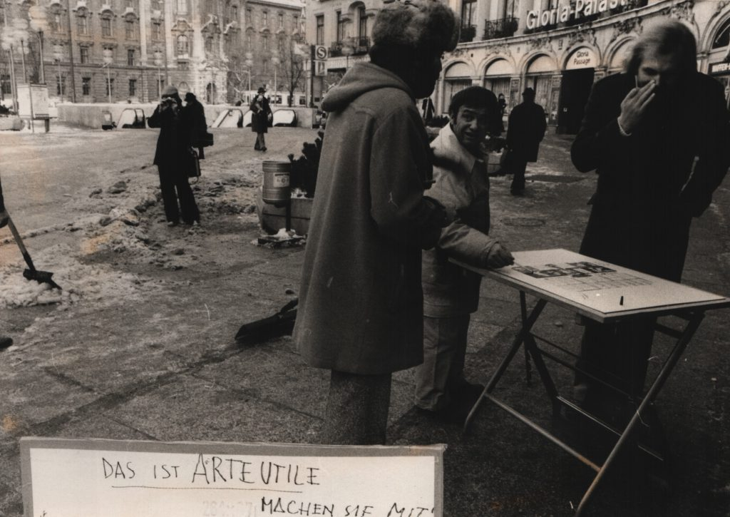 3 man stand around a folding table in the street. A board with handwritten sentence in front of them.