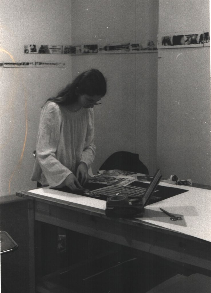 Woman standing in front of table working on a collage.
