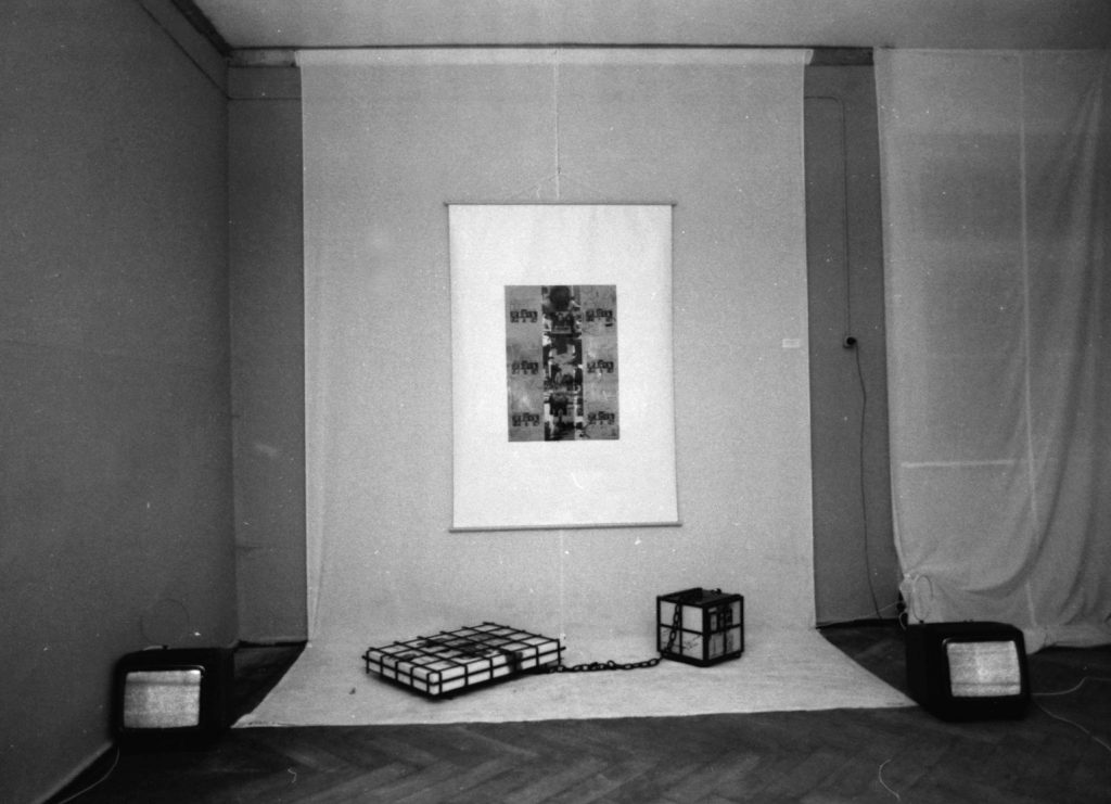 Long white linien cloth hanging down from ceiling covering partly floor. 1 large sheet with photocollage and handwritten text hangs on the cloth. 2 metal framed boxes on floor chained together.