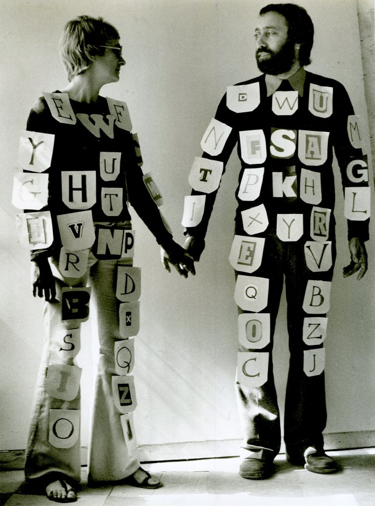 Couple holding hands. Notes with single letters attached all over their bodies.