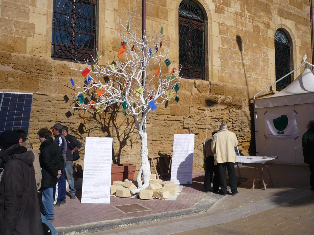 White painted tree stands on the sidewalk. Colourful notes hang on the branches. 2 boards with text on each side.
