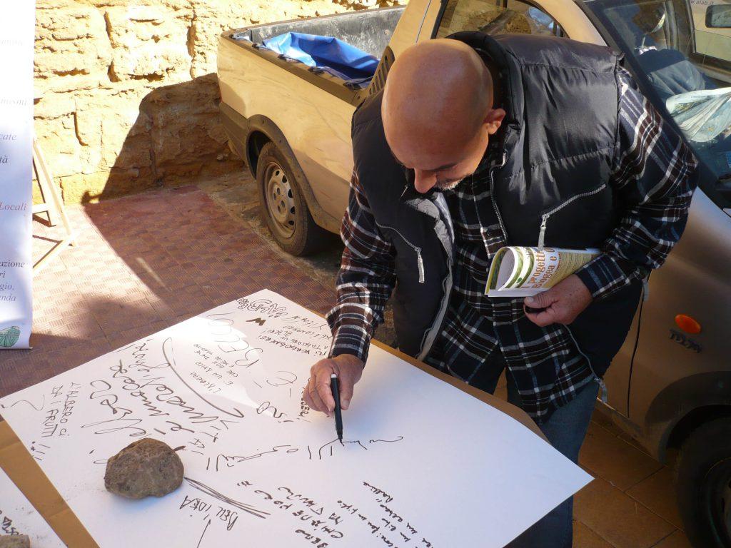 Man writes on the large paper sheet.