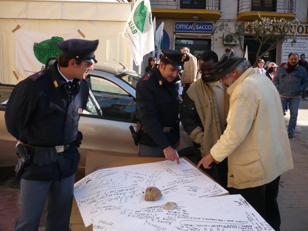Policemen discuss with other men in front of the table.
