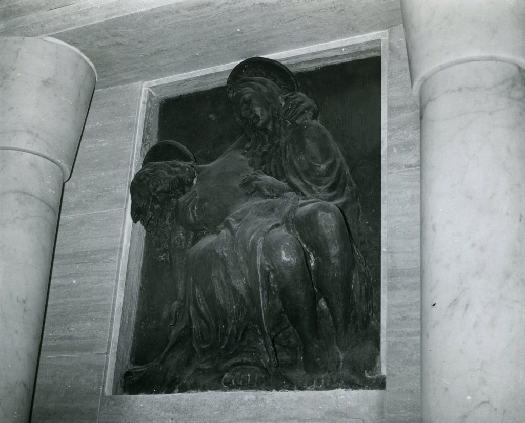 Stone fresco embedded in marble wall. Woman holding body of man in her arms.