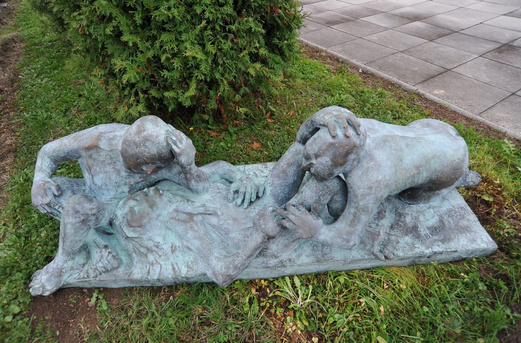 Sculpture of 2 figures taking care of another one lying on the ground.