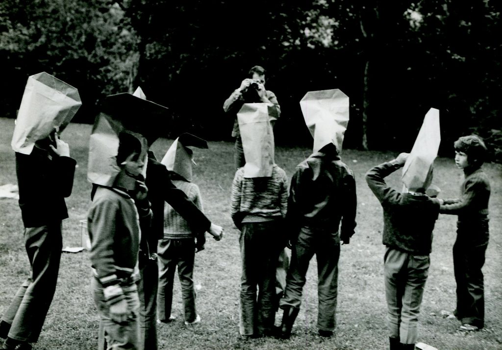 Kids with paper bags on head in park.