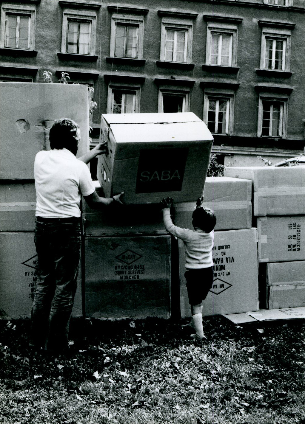 Man and kid buidling a tower of cardboard boxes.