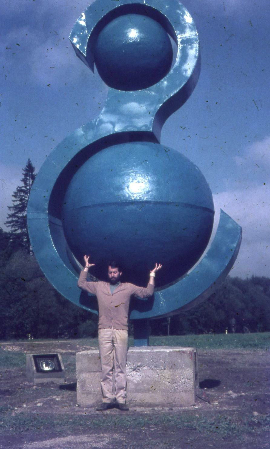 Man standing in front of sculpture. Large Letter S with 2 balls enclosed.