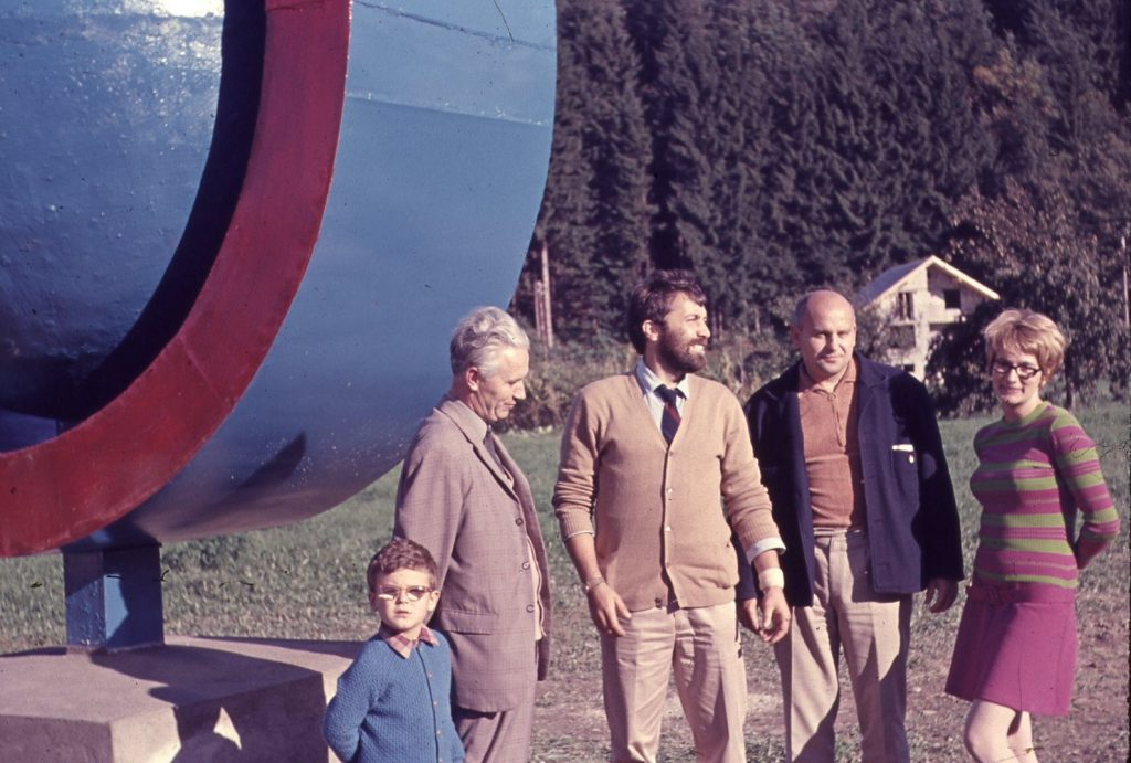 Group of people standing beside large sculpture.