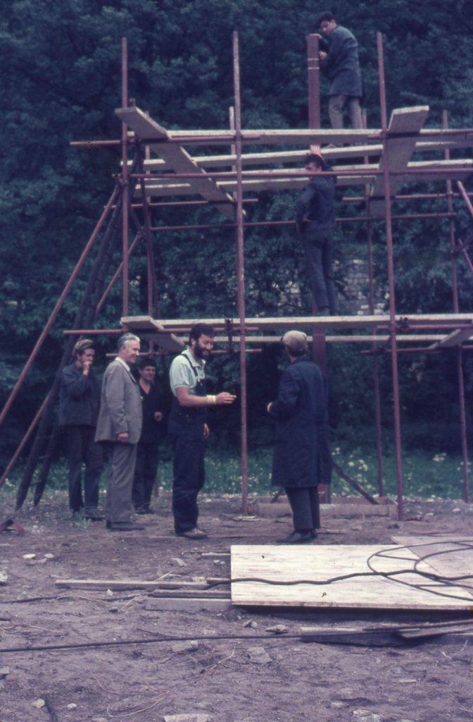 Men standing in front of scaffolding.