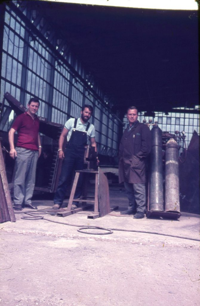 3 men with tools in a large production hall.
