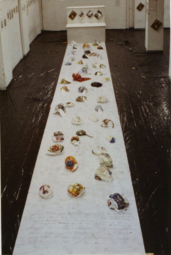 Black Plastic foil covers the floor of a white room. In the middle lies a white long cloth in front of a podest. On the paper web plastic bags are spreaded around.