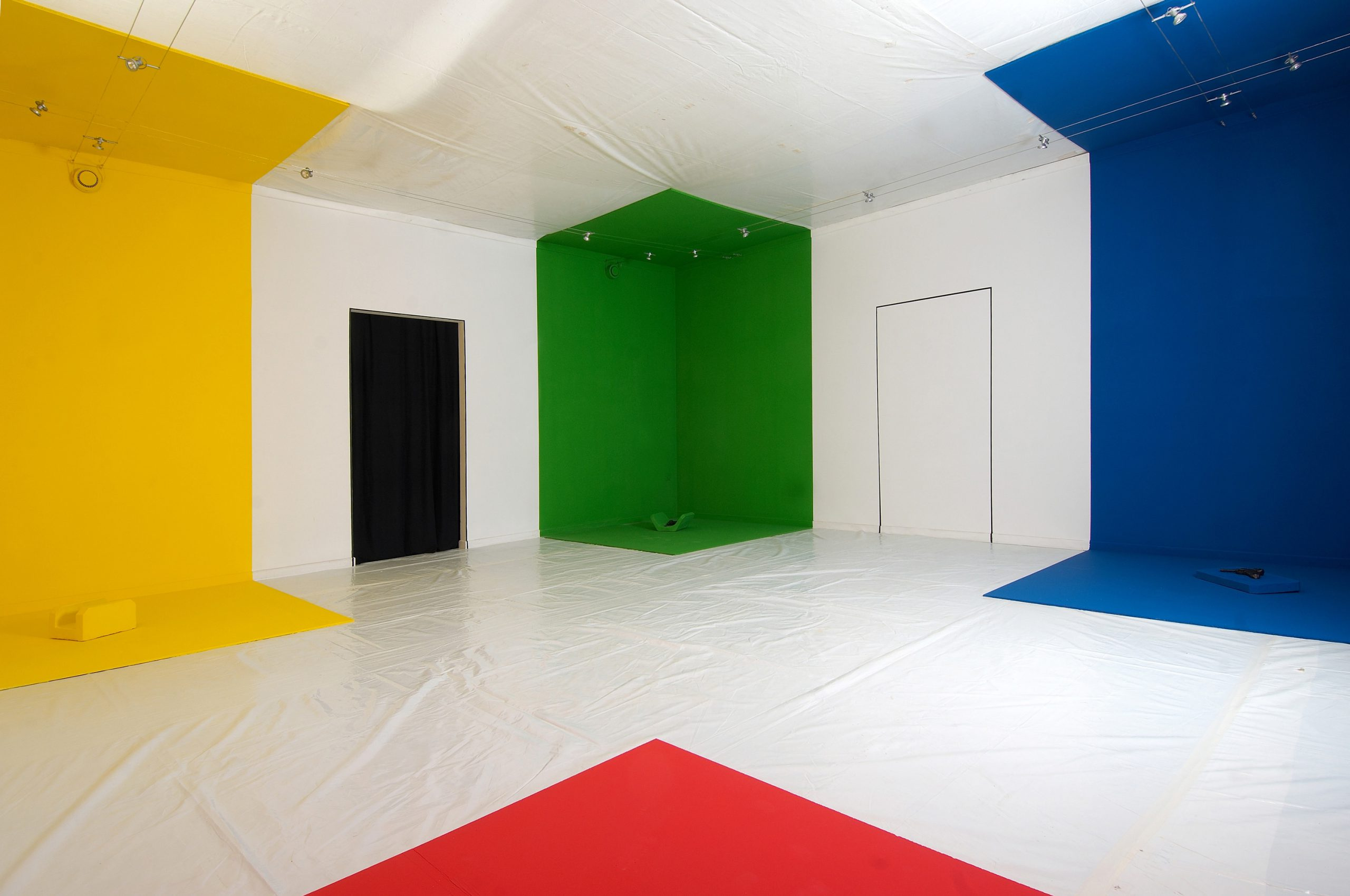 4 corner spaces in a white room painted in different colour. On the floor of every space lies a form-piece in same colour.