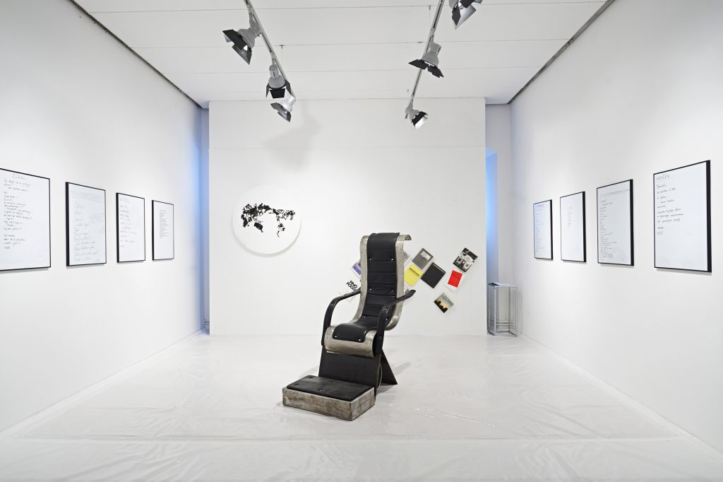 A lounge-type chair in the center of a totally white room. Framed handwritten texts hang on left and right wall. Catalogues and a type of map hang on the back wall.