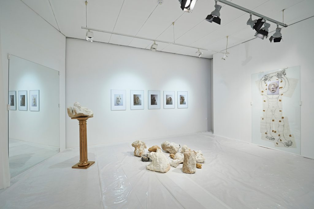 Antique golden column in a totally white room. A stone is placed on the column various others in front on the floor. Behind the column by the left wall stands a mirror. On the right wall hangs a framed collaged drawing. On the back wall framed photos of stone sculptures.